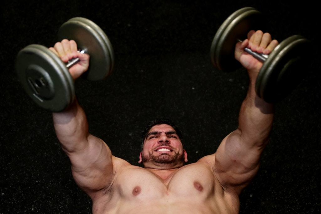 Body Builder Chris Kavvalos Continues Training Regime During Cor - SYDNEY, AUSTRALIA - MAY 24: Chris Kavvalos performs a dumbbell fly press  during a workout...