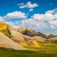 Badlands National Park - Peaks and valleys of delicately banded colors—colors that shift in the sunlight belie the challenges of crossing these peaks,...