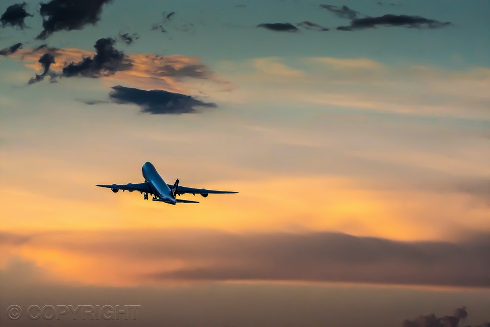 Aircraft in sunset - Aeroplane rising up into the clouds at sunset by commercial photographer, Cathy Finch Photography.