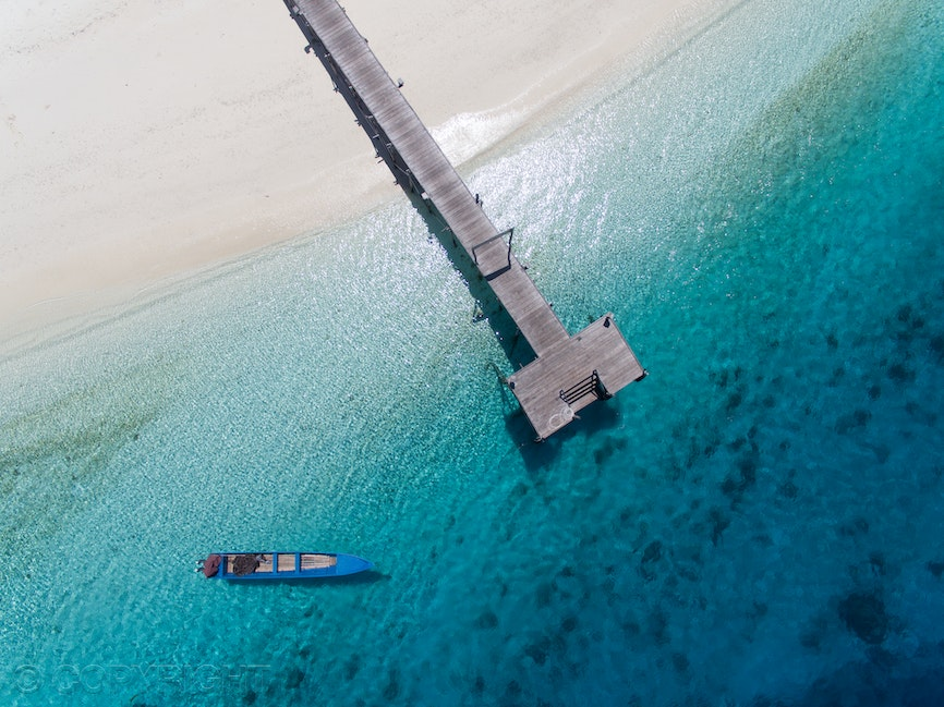 Jetty Raja Ampat - Jetty extending out over translucent blue ocean in Raja Ampat, West Papua, Indonesia, with blue boat floating beside.  Image by Cathy...