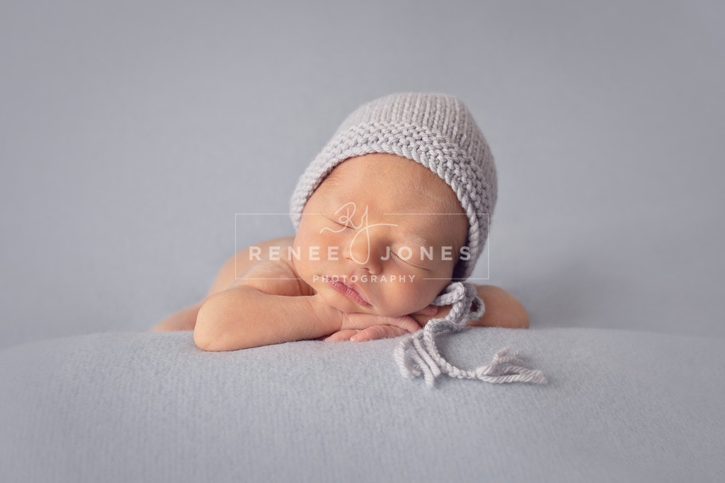 Chin on Hands - Brisbane Newborn Photographer - Sleeping baby in a bonnet with chin on his hands