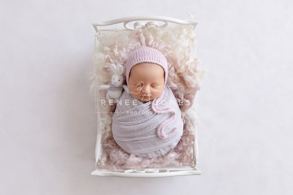 Rustic white mini scroll bed - Brisbane Newborn Photographer - Gorgeous image of a little girl wearing pinks and grey and sleeping on a small rustic white...