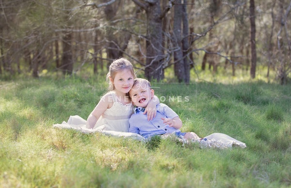 On-location sibling session - Siblings photographed in a grassy field in the morning light.