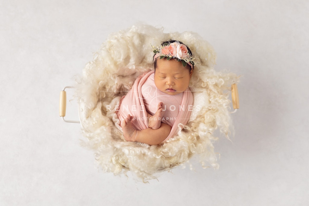 Baby in a cream pail - Brisbane Baby Photographer - Baby wrapped in pink with a floral headband sleeping in a fur lined tub on a white textured background