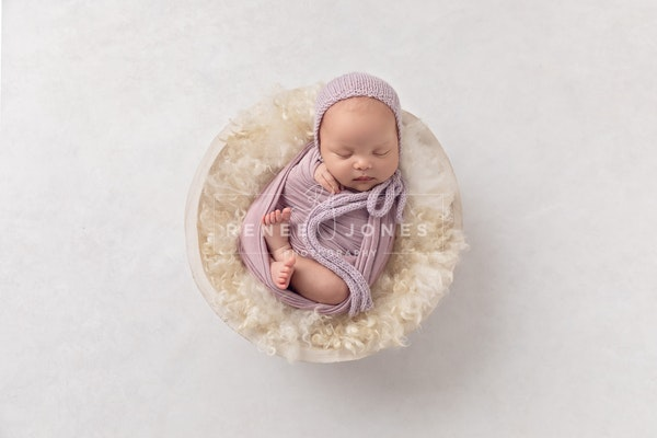 DAVIS_B-17 - Overhead photograph of a baby wrapped in purple and curled in a white wood bowl on a textured white background.
