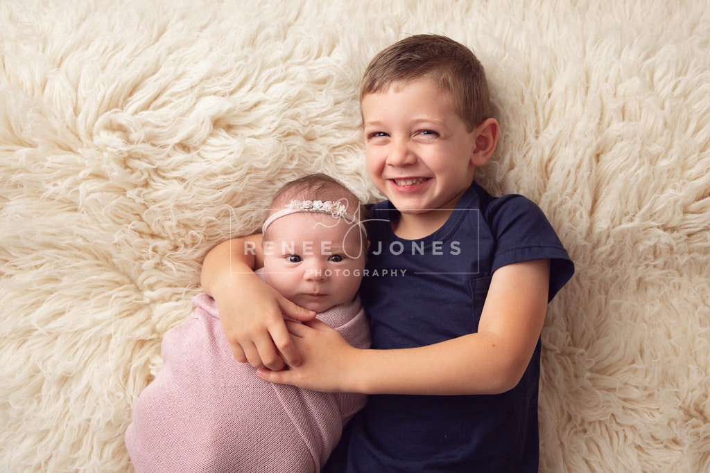 Big brother and newborn sister - Brisbane Newborn Photographer - Big brother cuddling newborn baby sister on a white fur rug