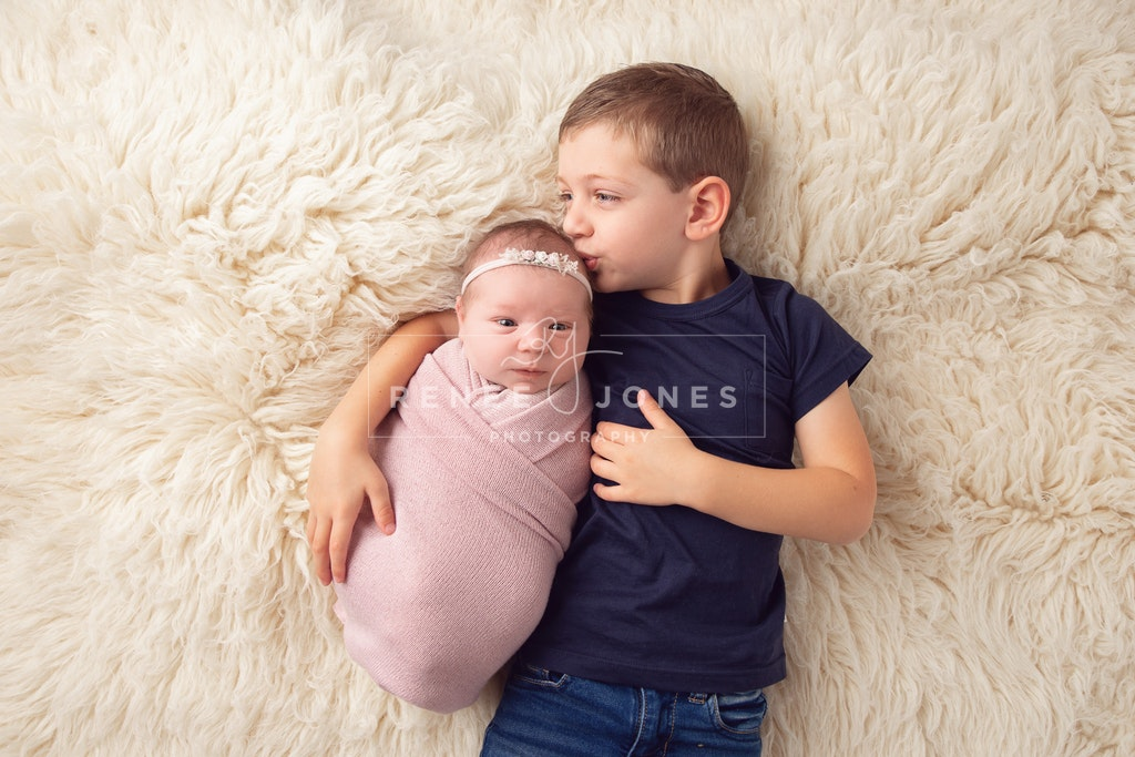 Newborn siblings - Brisbane Newborn Photographer - Older brother kissing his  newborn sister lying on a white fur rug.