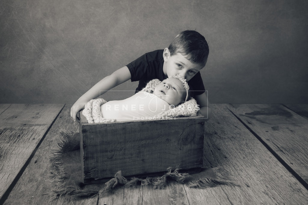 Sibling kiss - Brisbane Newborn Photographer - Black and white image of a big brother kissing his newborn sister who is sleeping in a rustic timber crate.