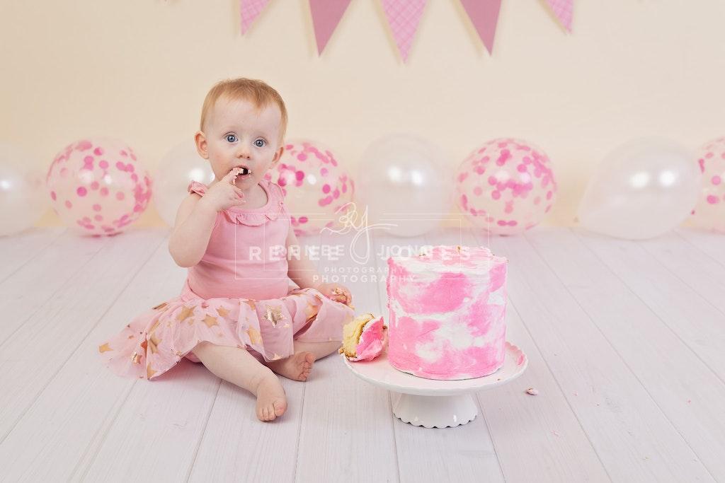Imogen's Cake Smash 2 - Brisbane Cake Smash Photographer - Baby girl tasting a birthday 'smash' cake. Brisbane Cake Smash Photographer