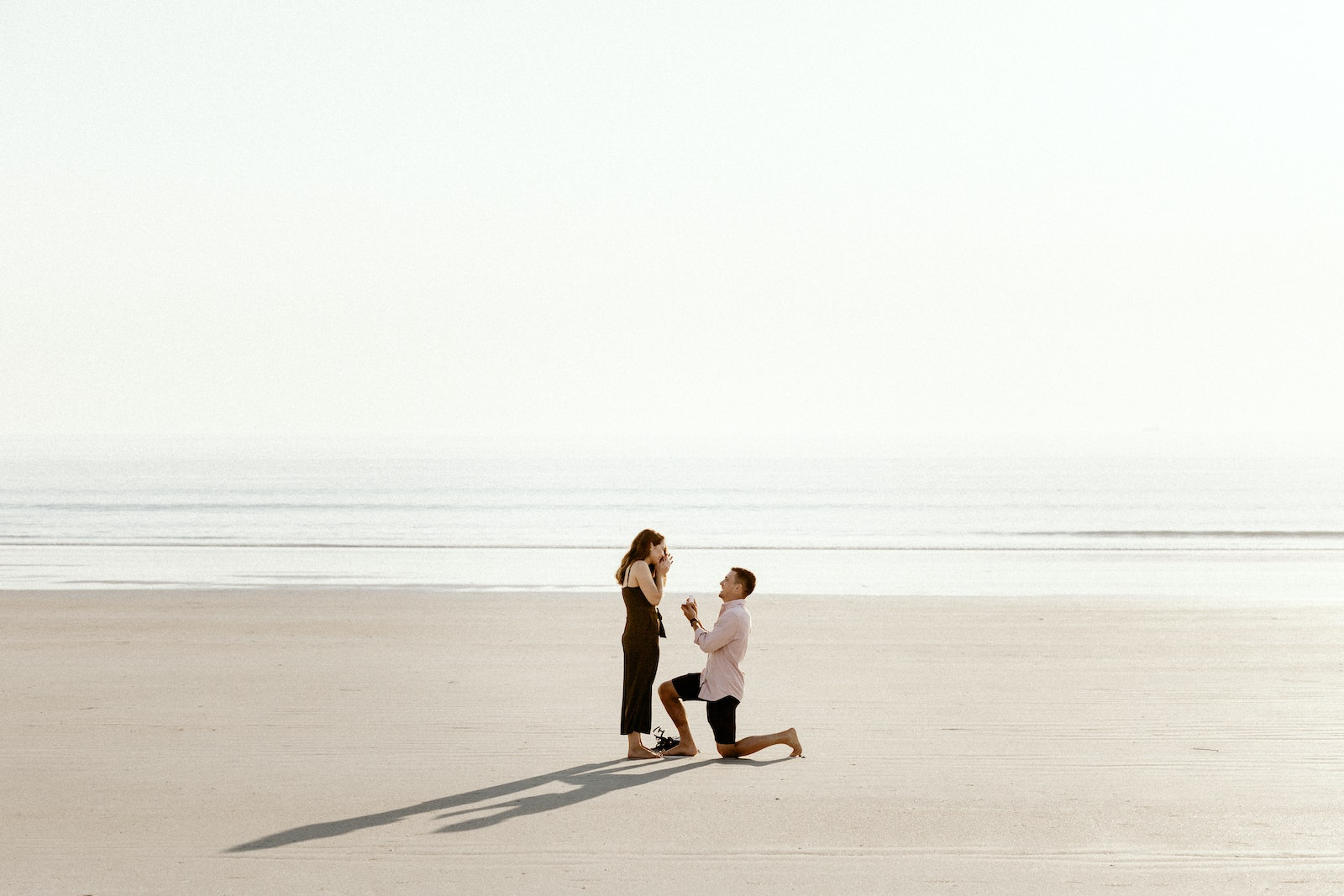 01 - Man on one knee proposing to his partner in the sand in front of the ocean.