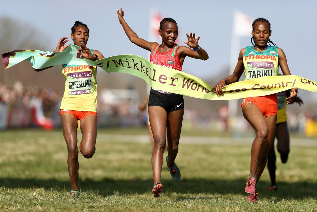 Junior Women's Finish - Beatrice Chebet of Kenya (C) crosses the line to win the Women's U20 Final as Alemitu Tariku of Ethiopia (R) reacts to coming second...