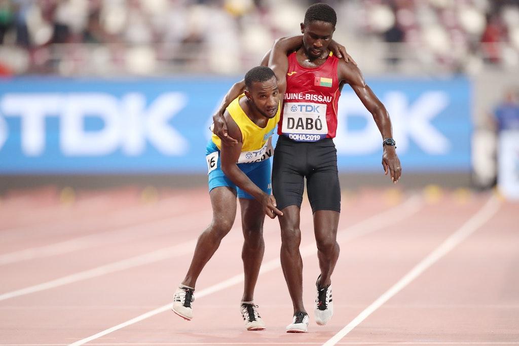 17th IAAF World Athletics Championships Doha 2019 - Day One - DOHA, QATAR - SEPTEMBER 27: Braima Suncar Dabo of Guinea-Bissau helps Jonathan Busby of Aruba...