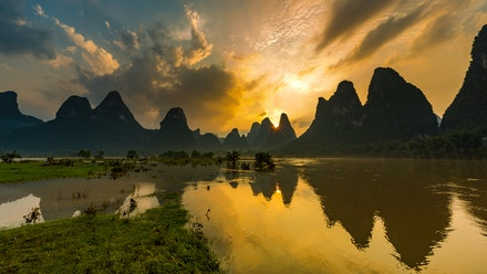 Sunset over the Li River - The sun sets over the amazing karst landscape surrounding the Li River in Guangxi Province near Yangshuo. A stunningly beautiful...