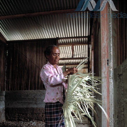 WK-editorial-18 - Adult plaiting palm fronds under BHP Steel roof in East Timor.